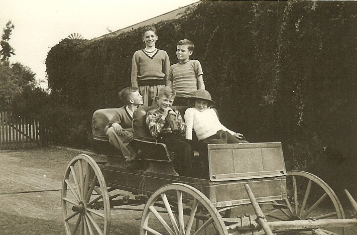 CJ II, Michael, Peter, Susan and a neighbor pose for a photo on an antique wagon.