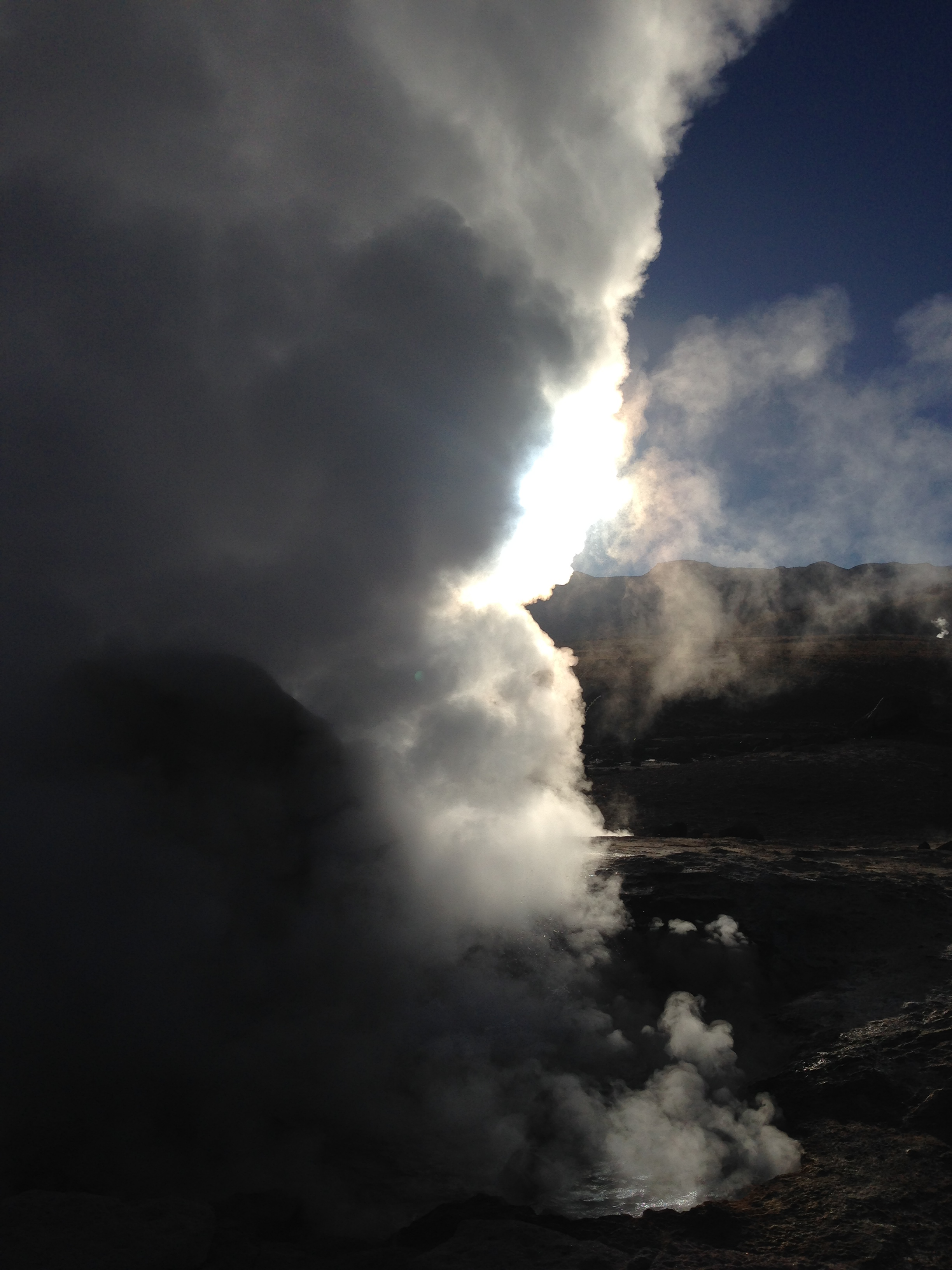 The sun sets behind a boiling geyser (that you can walk straight up to) at <em>El Tatio</em>.