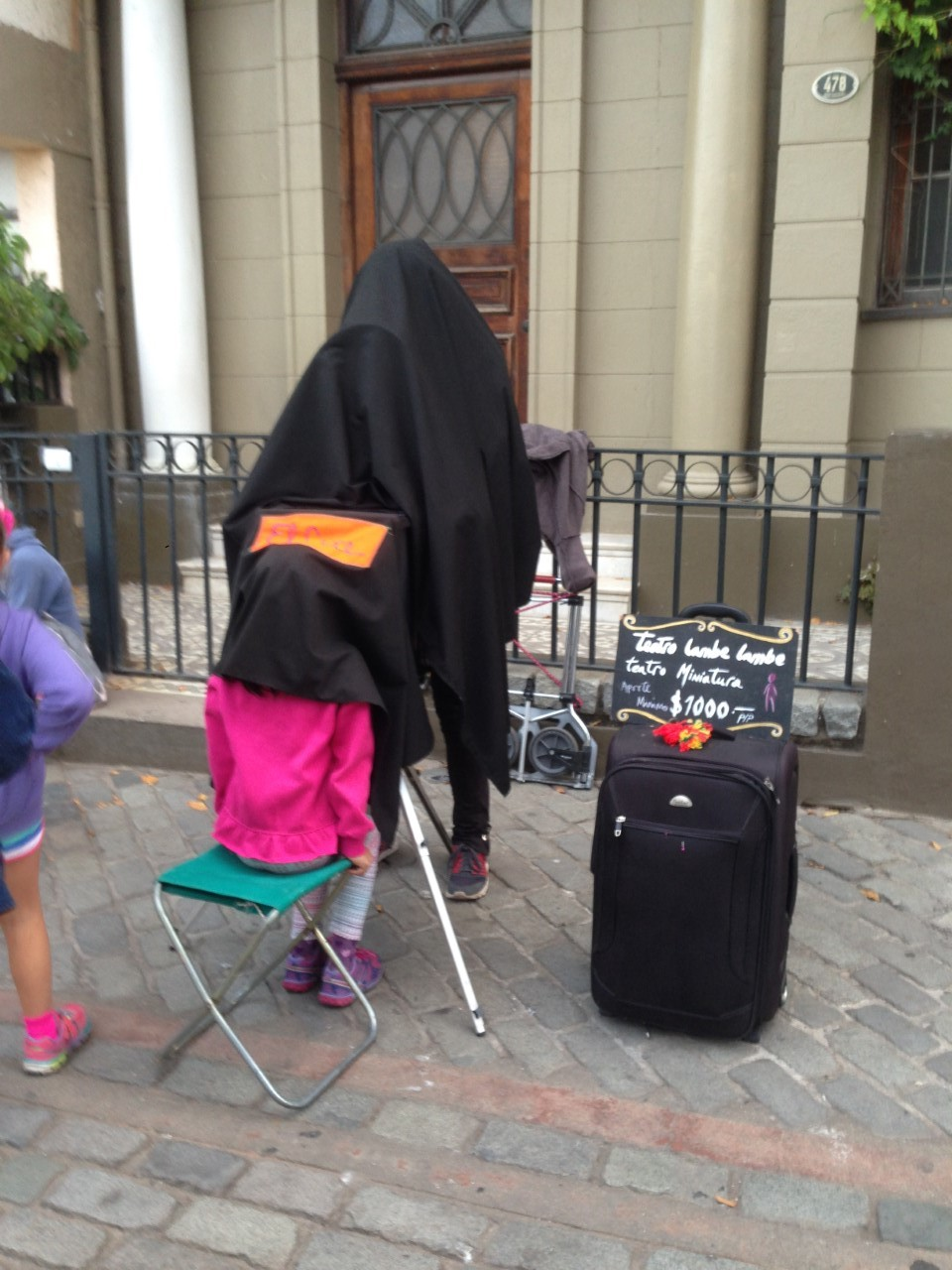 A child watches a puppet show - seriously! - under this sheet on a sidewalk.