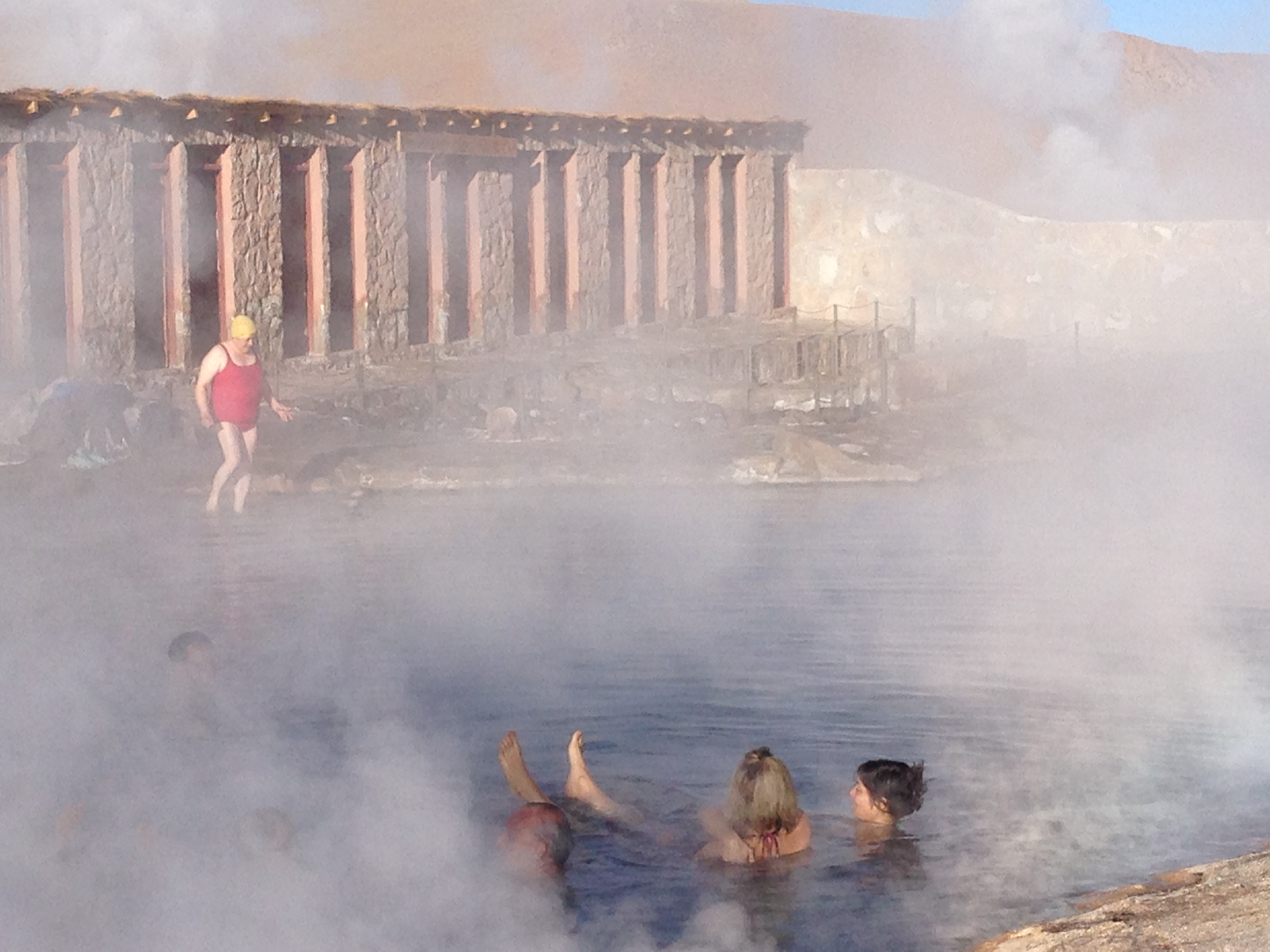 A Russian tourist in her red swimsuit and yellow swim cap gingerly enters the hot springs at <em>El Tatio</em>.